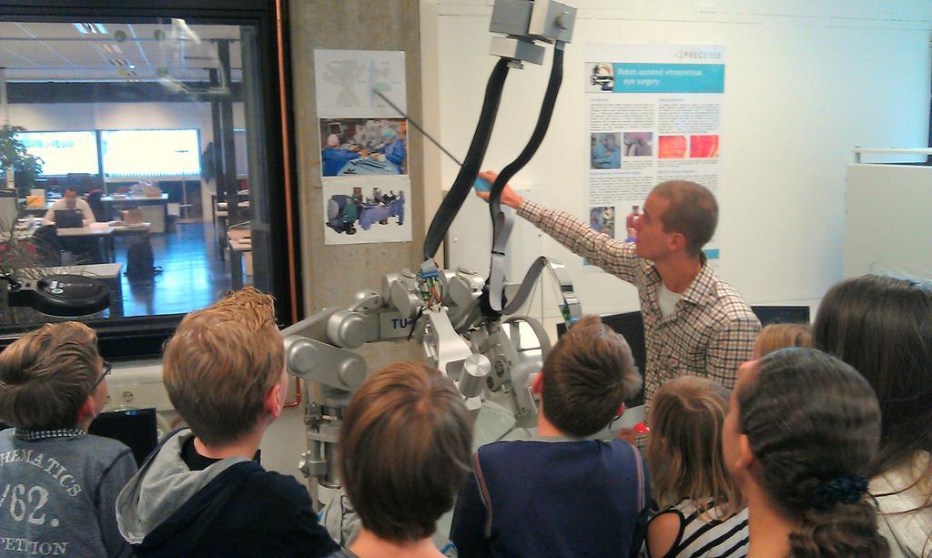 Maarten Beelen demonstreert de oogrobot aan jonge scholieren